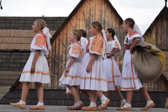 c44b79d02 Dievčatá v krojoch kráčajú a spievajú na javisku
